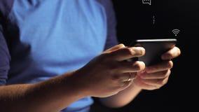Κινηματογράφηση σε πρώτο πλάνο των χεριών νεαρών άνδρων που δακτυλογραφούν sms να τυλίξει το τηλέφωνο εικόνων απόθεμα βίντεο