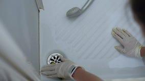 Κινηματογράφηση σε πρώτο πλάνο των χεριών νοικοκυρών με τα γάντια που καθαρίζουν το νεροχύτη ντους απόθεμα βίντεο