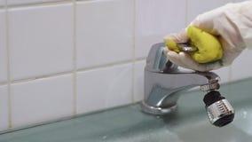 Κινηματογράφηση σε πρώτο πλάνο των χεριών νοικοκυρών με τα γάντια που καθαρίζουν τη στρόφιγγα απόθεμα βίντεο