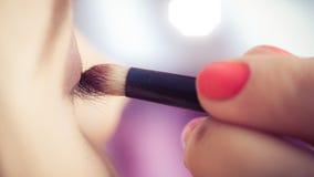 Κινηματογράφηση σε πρώτο πλάνο των χεριών που εφαρμόζουν τη σκόνη σκιάς ματιών στο θηλυκό του προσώπου δέρμα στοκ φωτογραφίες