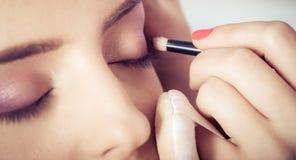 Κινηματογράφηση σε πρώτο πλάνο των χεριών που εφαρμόζουν τη σκόνη σκιάς ματιών στο θηλυκό του προσώπου δέρμα στοκ φωτογραφία με δικαίωμα ελεύθερης χρήσης