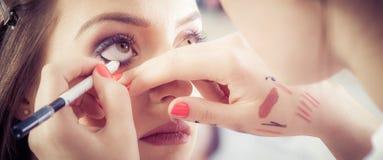 Κινηματογράφηση σε πρώτο πλάνο των χεριών που εφαρμόζουν τη σκόνη σκιάς ματιών στο θηλυκό του προσώπου δέρμα στοκ φωτογραφία