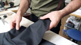 Κινηματογράφηση σε πρώτο πλάνο των χεριών ραφτών ` s με τις καρφίτσες που ράβουν το ύφασμα δύο στο ράψιμο του στούντιο απόθεμα βίντεο