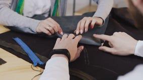 Κινηματογράφηση σε πρώτο πλάνο των χεριών των σχεδιαστών μόδας tailores που εργάζονται με τα υλικά, αυτοί συνεδρίαση στο όμορφο α απόθεμα βίντεο