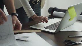 Κινηματογράφηση σε πρώτο πλάνο των χεριών της γυναίκας και του άνδρα που εργάζονται στο lap-top, και νέα προγράμματα που επισύρον φιλμ μικρού μήκους