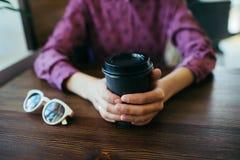 Κινηματογράφηση σε πρώτο πλάνο των χεριών της γυναίκας με το φλιτζάνι του καφέ στοκ εικόνες