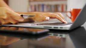 Κινηματογράφηση σε πρώτο πλάνο των χεριών της γυναίκας που χρησιμοποιεί την πιστωτική κάρτα και τον υπολογιστή που αγοράζουν on-l απόθεμα βίντεο