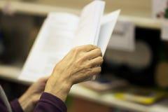 Κινηματογράφηση σε πρώτο πλάνο των χεριών του ηλικιωμένου προσώπου με το ανοικτό βιβλίο, βιβλιοπωλείο Πραγματική σκηνή Έννοια εκπ Στοκ Εικόνες