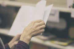 Κινηματογράφηση σε πρώτο πλάνο των χεριών του ηλικιωμένου προσώπου με το ανοικτό βιβλίο, βιβλιοθήκη Τονισμένο υπόβαθρο Έννοια εκπ Στοκ Εικόνες