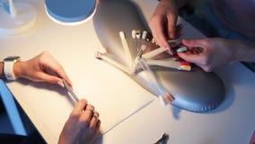 Κινηματογράφηση σε πρώτο πλάνο των χεριών του θηλυκού πελάτη που επιλέγουν το χρώμα για το μανικιούρ φιλμ μικρού μήκους