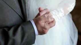 Κινηματογράφηση σε πρώτο πλάνο των χεριών των newlyweds στη ημέρα γάμου φιλμ μικρού μήκους