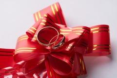 Κινηματογράφηση σε πρώτο πλάνο των χρυσών γαμήλιων δαχτυλιδιών ζευγαριού στο κόκκινο τόξο γαμήλιων κορδελλών Στοκ Εικόνα