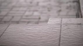 Κινηματογράφηση σε πρώτο πλάνο, υπάρχει δυνατή βροχή, ένα ντους, μεγάλη βαριά σταλαγματιά πτώσεων επάνω στα κεραμίδια οδών πτώση  φιλμ μικρού μήκους