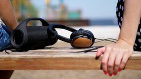 Κινηματογράφηση σε πρώτο πλάνο, υπάρχουν μεγάλα ακουστικά και ένα μικρό, μίνι μεγάφωνο κυλίνδρων μουσικής bluetooth φορητό μαύρο  φιλμ μικρού μήκους