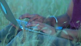Κινηματογράφηση σε πρώτο πλάνο, χέρια μιας ινδικής συνεδρίασης Paren στο κείμενο δακτυλογράφησης χλόης στο πληκτρολόγιο lap-top απόθεμα βίντεο