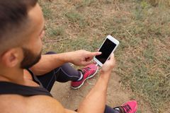 Κινηματογράφηση σε πρώτο πλάνο bodybuilder που καλεί ένα τηλέφωνο Μυϊκό άτομο που χρησιμοποιεί την τεχνολογία σε ένα θολωμένο υπό Στοκ εικόνα με δικαίωμα ελεύθερης χρήσης