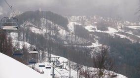 Κινηματογράφηση σε πρώτο πλάνο cableway των ανυψωτικών καμπινών στα βουνά ενάντια στους λόφους που καλύπτονται από το χιόνι και τ φιλμ μικρού μήκους