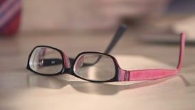 Κινηματογράφηση σε πρώτο πλάνο eyeglasses στον πίνακα, συμπαθητικά εξαρτήματα για το πρόσωπο με την κακή όραση απόθεμα βίντεο