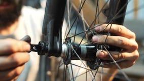 Κινηματογράφηση σε πρώτο πλάνο mahanic καθορίζοντας μια ρόδα ποδηλάτων στο εργαστήριο επισκευής της απόθεμα βίντεο