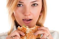 Κινηματογράφηση σε πρώτο πλάνο γυναικών που τρώει ένα χάμπουργκερ Στοκ Εικόνες