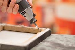 Κινηματογράφηση σε πρώτο πλάνο ενός ατόμου hardworker που τρυπά ένα ξύλινο πλαίσιο με το τρυπάνι του πέρα από έναν γκρίζο πίνακα  Στοκ φωτογραφία με δικαίωμα ελεύθερης χρήσης