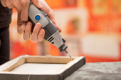 Κινηματογράφηση σε πρώτο πλάνο ενός ατόμου hardworker που τρυπά ένα ξύλινο πλαίσιο με το τρυπάνι του πέρα από έναν γκρίζο πίνακα  Στοκ φωτογραφίες με δικαίωμα ελεύθερης χρήσης