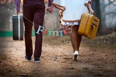 Κινηματογράφηση σε πρώτο πλάνο ενός ζευγαριού των newlyweds που περπατούν με τις βαλίτσες Στοκ Εικόνες