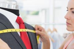 Κινηματογράφηση σε πρώτο πλάνο ενός θηλυκού σχεδιαστή μόδας που μετρά το κοστούμι στο ομοίωμα Στοκ Εικόνες