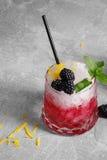 Κινηματογράφηση σε πρώτο πλάνο ενός κρύου ποτού μούρων Ποτό με τη μέντα, τη φλούδα λεμονιών και τα βατόμουρα σε ένα γκρίζο υπόβαθ Στοκ Φωτογραφία