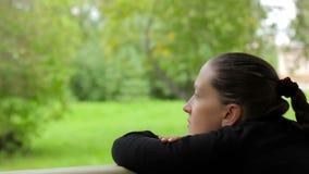 Κινηματογράφηση σε πρώτο πλάνο ενός σκεπτικού κοριτσιού με ένα ονειροπόλο βλέμμα στο υπόβαθρο των πράσινων δέντρων απόθεμα βίντεο