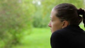 Κινηματογράφηση σε πρώτο πλάνο ενός σκεπτικού κοριτσιού με ένα ονειροπόλο βλέμμα στο υπόβαθρο των πράσινων δέντρων φιλμ μικρού μήκους