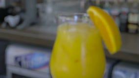 Κινηματογράφηση σε πρώτο πλάνο ενός φρέσκου χυμού από πορτοκάλι με τους κύβους πάγου φιλμ μικρού μήκους