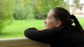 Κινηματογράφηση σε πρώτο πλάνο ενός χαμογελώντας κοριτσιού με ένα ονειροπόλο βλέμμα στο υπόβαθρο των πράσινων δέντρων απόθεμα βίντεο