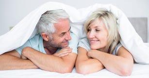 Κινηματογράφηση σε πρώτο πλάνο ενός ώριμου ζεύγους που βρίσκεται στο κρεβάτι Στοκ Φωτογραφίες