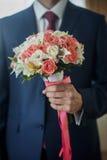 Κινηματογράφηση σε πρώτο πλάνο ενός fiance στο κοστούμι με τα γαμήλια λουλούδια Στοκ Εικόνες