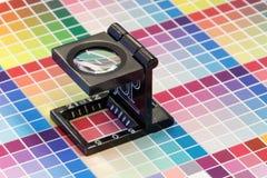 Κινηματογράφηση σε πρώτο πλάνο ενός loupe σε μια ζωηρόχρωμη τυπωμένη ύλη δοκιμής Στοκ εικόνα με δικαίωμα ελεύθερης χρήσης