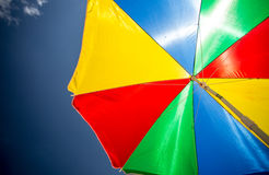 Κινηματογράφηση σε πρώτο πλάνο ζωηρόχρωμο parasol ήλιων στην παραλία ενάντια στο μπλε ουρανό Στοκ Φωτογραφία