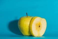 Κινηματογράφηση σε πρώτο πλάνο, η κίτρινη Apple σε ένα μπλε υπόβαθρο Στοκ Φωτογραφία