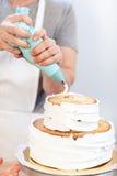 Κινηματογράφηση σε πρώτο πλάνο, διακόσμηση ενός κέικ με την άσπρη κρέμα που χρησιμοποιεί μια σύριγγα ζύμης Το χέρι ατόμων έβαλε τ Στοκ φωτογραφία με δικαίωμα ελεύθερης χρήσης