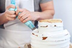 Κινηματογράφηση σε πρώτο πλάνο, διακόσμηση ενός κέικ με την άσπρη κρέμα που χρησιμοποιεί μια σύριγγα ζύμης Το χέρι ατόμων έβαλε τ Στοκ φωτογραφίες με δικαίωμα ελεύθερης χρήσης