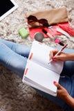 Κινηματογράφηση σε πρώτο πλάνο μιας γυναίκας που γράφει στο ημερολόγιο γραφείων της Στοκ Εικόνες