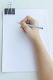 Κινηματογράφηση σε πρώτο πλάνο μιας γυναίκας που γράφει στο κενό έγγραφο στοκ εικόνα
