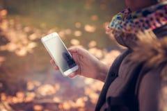 Κινηματογράφηση σε πρώτο πλάνο μιας όμορφης γυναίκας brunette που κρατά ένα smartphone περπατώντας στο πάρκο, τη λίμνη και τις αν Στοκ φωτογραφία με δικαίωμα ελεύθερης χρήσης