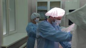 Κινηματογράφηση σε πρώτο πλάνο Ο χειρούργος γιατρών στη προστατευτική ενδυμασία, εκτελεί μια γυναικολογική λειτουργία φιλμ μικρού μήκους
