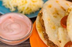 Κινηματογράφηση σε πρώτο πλάνο παραδοσιακά εύγευστα arepas, τεμαχισμένο τυρί αβοκάντο κοτόπουλου και τυριού Cheddar και τεμαχισμέ Στοκ εικόνα με δικαίωμα ελεύθερης χρήσης