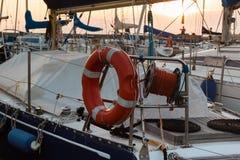 Κινηματογράφηση σε πρώτο πλάνο πορτοκαλιού Lifebuoy και του κυλημένου σχοινιού στην πλέοντας βάρκα Στοκ εικόνα με δικαίωμα ελεύθερης χρήσης