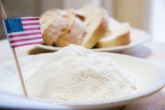 Κινηματογράφηση σε πρώτο πλάνο που πυροβολείται της αμερικανικής σημαίας και του αλευριού σε ένα πιάτο Φέτες του ψωμιού στο υπόβα Στοκ Εικόνα