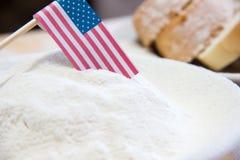 Κινηματογράφηση σε πρώτο πλάνο που πυροβολείται της αμερικανικής σημαίας και του αλευριού σε ένα πιάτο Φέτες του ψωμιού στο υπόβα Στοκ Φωτογραφία