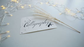 Κινηματογράφηση σε πρώτο πλάνο που πυροβολείται της κάρτας καλλιγραφίας με την καλλιγραφία επιγραφής στο άσπρο φύλλο του εγγράφου φιλμ μικρού μήκους