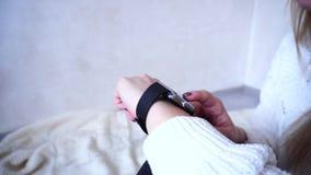 Κινηματογράφηση σε πρώτο πλάνο που πυροβολείται της συσκευής σε ετοιμότητα θηλυκό που εξετάζει το έξυπνο ρολόι στο φωτεινό δωμάτι απόθεμα βίντεο